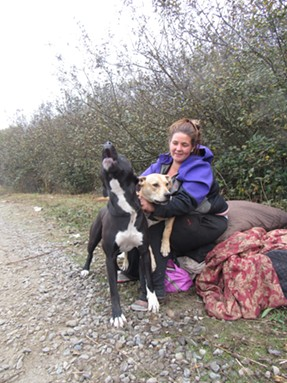 Marsh camper Brittany sits with her belongings and dogs Prince and Xena. - LINDA STANSBERRY