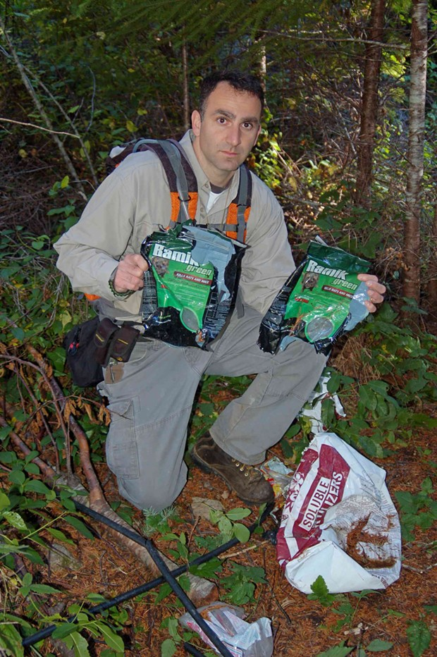 Mourad Gabriel poses with rodenticides found at a Supply Creek grow site in Humboldt County. - GRETA WENGERT/INTEGRAL ECOLOGY RESEARCH CENTER