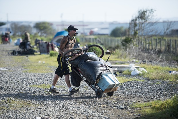 A homeless man moves out of the PalCo Marsh during the city's May 2 eviction. - FILE