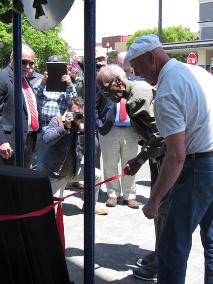 Howard pulls at the ribbon to unveil the new Old Town plaque in his honor. - LINDA STANSBERRY