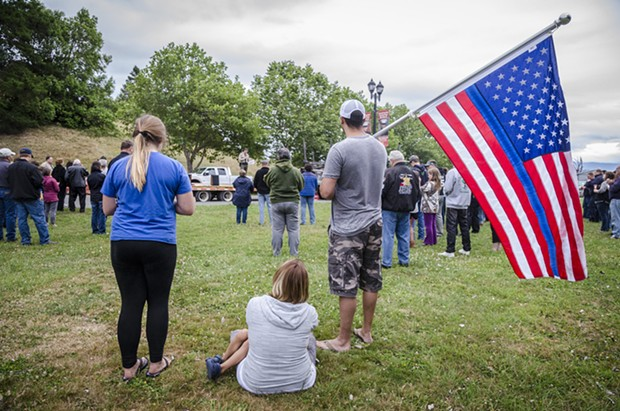 """Mike Grimaldo, of Fortuna, held a flag with a blue stripe at the candlelight vigil in Fortuna on Friday evening. """"The Thin Blue Line"""" is a symbol used to commemorate fallen law enforcement officers. - MARK LARSON"""