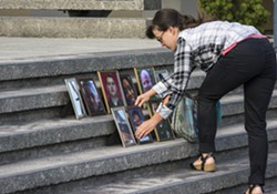 """Tamara McFarland, of Bayside, one of the informal organizers of the """"Solidarity Vigil for Our Beloved Community,"""" arrived early to place 11 framed portraits of recently killed black persons and the Dallas law enforcement officers on the county courthouse steps in Eureka. - MARK LARSON"""