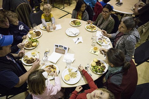 A table full of people enjoying a meal prepared by volunteers and staff from Arcata Elementary at the Bowl of Beans Benefit on Monday, Jan. 16. - SAM ARMANINO