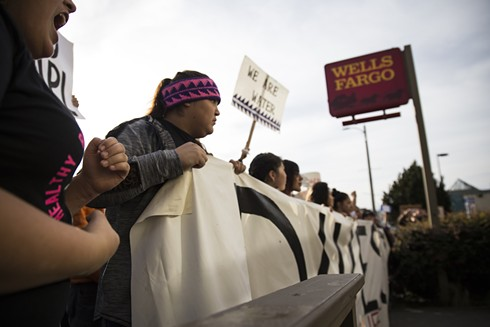 Kis-dyan-te' Joseph, 16, from the Hoopa Shoshone Piute and Karuk tribes, holds the right side of the banner reading 'Divest' in front of the Wells Fargo in Arcata on Saturday. - SAM ARMANINO
