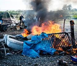 Belongings blaze on the final day of the PalCo Marsh encampment. - FILE
