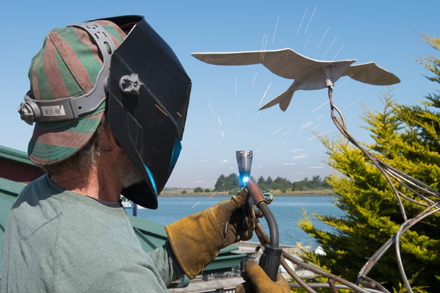 "Jack Sewell sparks up the welding torch to put the bird back on ""Keeping Up with Current Events."" - MARK MCKENNA"