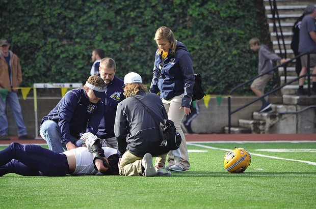 Trainers attend to an injured Augustana University football player in the round one playoff game at Redwood Bowl in 2015. Researchers are beginning to equate playing — and studying — with a concussion to running on a sprained ankle, and are recommending immediate rest upon signs of a brain injury. - FILE