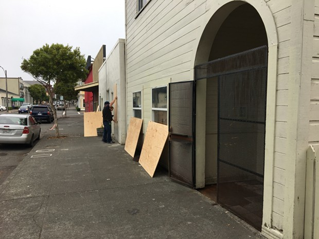 Workers board up 216, 218 and 220 Third St. after the city condemned the properties. - THADEUS GREENSON
