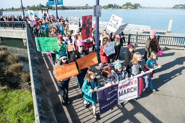 A group of young girls carries the Women's March banner at the head of the procession. - PHOTO BY MARK MCKENNA
