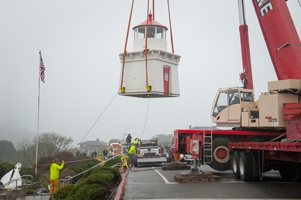 Two workers tie ropes to align the lighthouse as it is moved to a trailer. - MARK MCKENNA