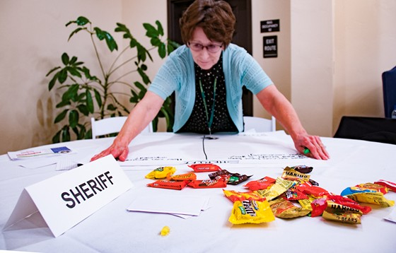 An assistant to Sheriff Billy Honsal prepares to write down residents' concerns on a table strewn with candy for those who missed dinner. - KYM KEMP