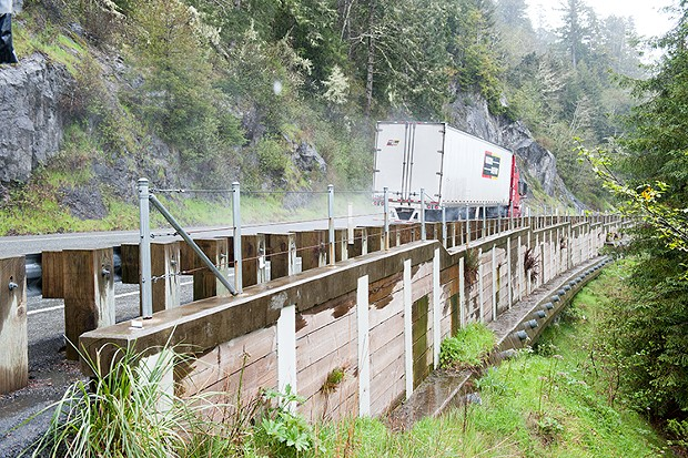 A tractor trailer passes one of the retaining walls on the grade. - PHOTO BY MARK MCKENNA