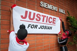 """Students hang a """"Justice for Josiah"""" banner on the Humboldt State University quad earlier this month. A similar banner hung outside the D Street Neighborhood Center for the Community Dialogue on Race. - PHOTO BY MARK MCKENNA"""