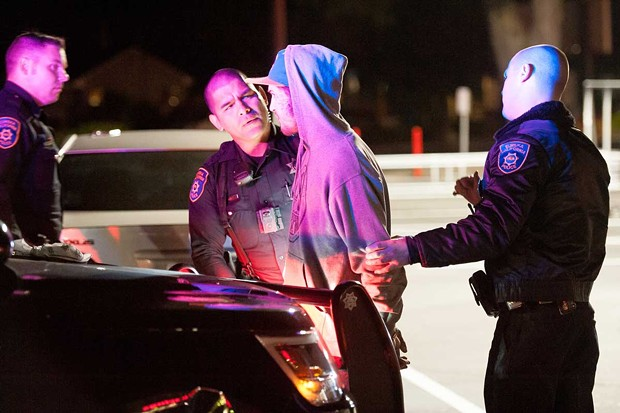 EPD officer Raymond Nunez prepares to arrest a man after he refused to leave the WinCo parking lot. - PHOTO BY MARK MCKENNA