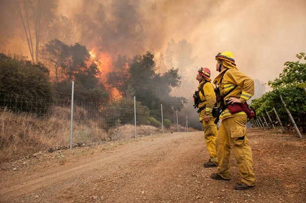 Chris Mitchell, left, and Arly Allen watch the progress of the fire as it slowly burns towards a private road on the Cache Creek Winery in Lake County. - MARK MCKENNA