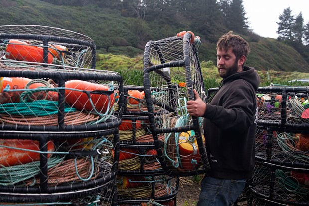 Curt Wilson stacks crab traps in preparation for the opening of the commercial crab season.