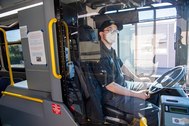 A Humboldt Transit Authority driver sits behind a Plexiglass shield wearing a facial covering, which drivers with glasses are not required to wear while buses are in motion due to safety concerns.