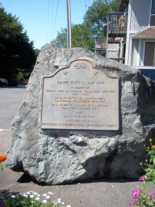 A historic plaque describes Camp Curtis, which sat in the hills of Arcata from 1862 to 1865 and housed the 1st Battalion California Volunteer Mountaineers, which committed acts of genocide.