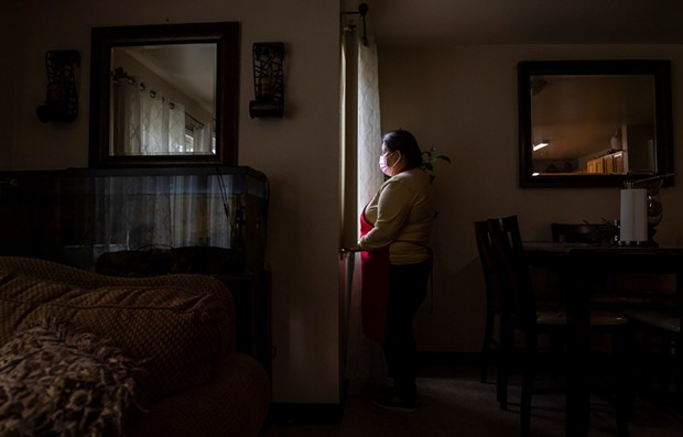 Blanca Esthela Trejo, 46, is photographed looking outside the windows near her dining room table inside her home in Salinas on April 22. Photo by David Rodriguez, The Salinas Californian