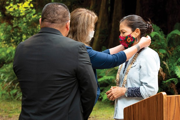 Yurok Tribal Councilmember Sherri Provolt places a necklace made from abalone and bear grass and on U.S. Interior Secretary Deb Haaland as a gift from the tribe during Haaland's visit to the North Coast in August.