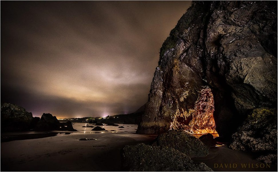 The cave mouth, with the lights of Trinidad and surroundings in the distance. Note the cleft in the rock above the mouth. It is also plainly visible on the inside all the way to be back. It was a cloudy night. I'm usually looking for the Milky Way in a sky, but this cottony substance covering the view had its own charm. - COURTESY OF DAVID WILSON