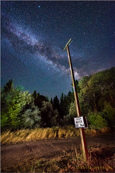 """High Water Dec 1964,"" reads the sign at chest level. Arrows on the pole draw the eye to the true marker far above. Avenue of the Giants at Weott, Humboldt County, California. - DAVID WILSON"
