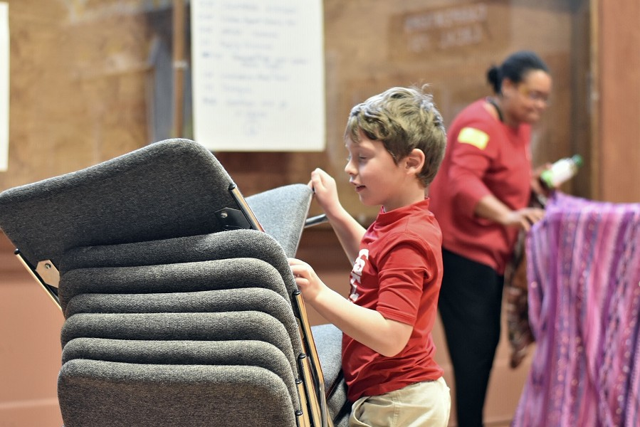 Six-year-old Miles Edrington, who has attended the planing meetings with his mother Allison Edrington, helps put chairs away. - PHOTO BY MEGAN BENDER