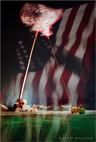 A giant U.S. flag flies beside U.S. Highway 101 between Arcata and McKinleyville, Humboldt County, California. 1991. Shot on 35mm film, this is an in-camera double exposure on a single negative; I made one exposure of the whole scene with the crane carrying the flag twisting in the wind. Then, without advancing the film, I took a telephoto shot of the flag filling the frame with its stripes flowing softly upward. The two images overlapped on the negative to produce this image. - DAVID WILSON