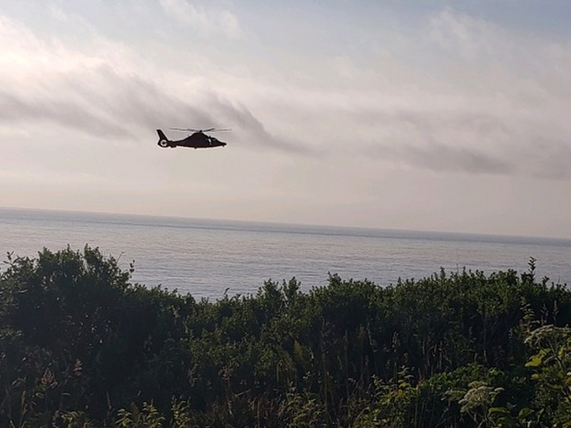 A MH-65 Dolphin helicopter, like this one pictured on a different rescue, plucked the men from the island. - U.S. COAST GUARD PHOTO COURTESY OF ARCATA MAD RIVER AMBULANCE SERVICES