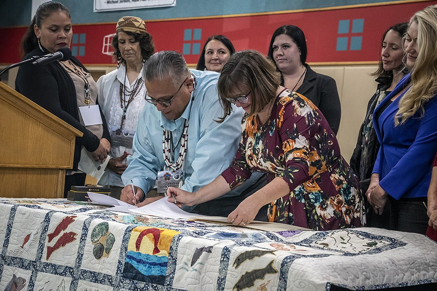 Wiyot Tribal Chair Ted Hernandez and Eureka Mayor Susan Seaman sign the land transfer paperwork. - BY MARK LARSON