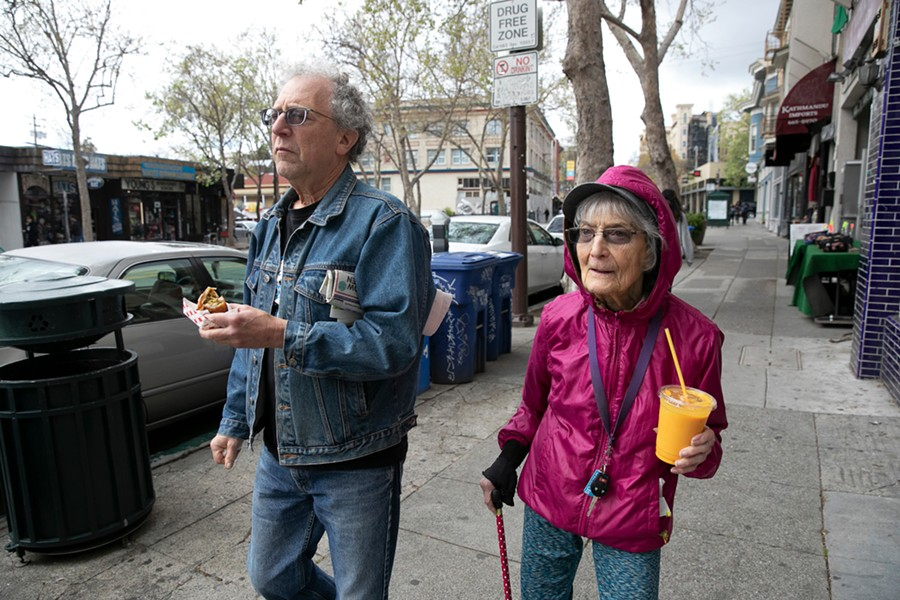 Dolores Helman, 93, and her son Elliot Helman, 64, go for a walk in Berkeley on March 15, 2020, as Gov. Gavin Newsom calls for isolation of all elderly people and those with chronic health conditions in response to growing concern over the coronavirus. - ANNE WERNIKOFF FOR CALMATTERS