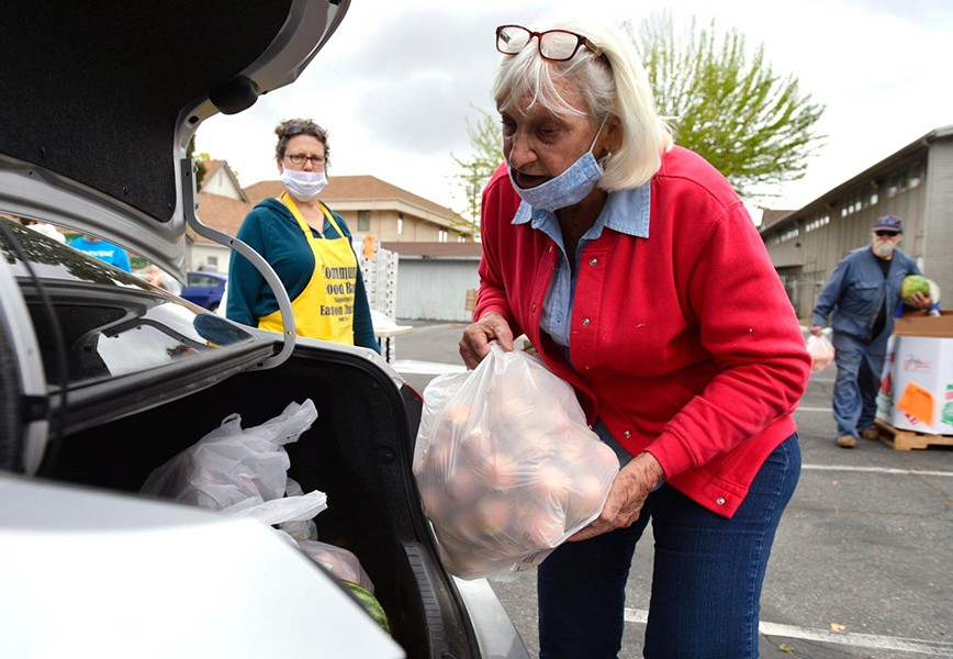 Volunteer Cheryl Phelps, right, helps load food at a food bank giveaway held at Easton Presbyterian Church Monday, April 6, 2020 in Easton. - ERIC PAUL ZAMORA, THE FRESNO BEE