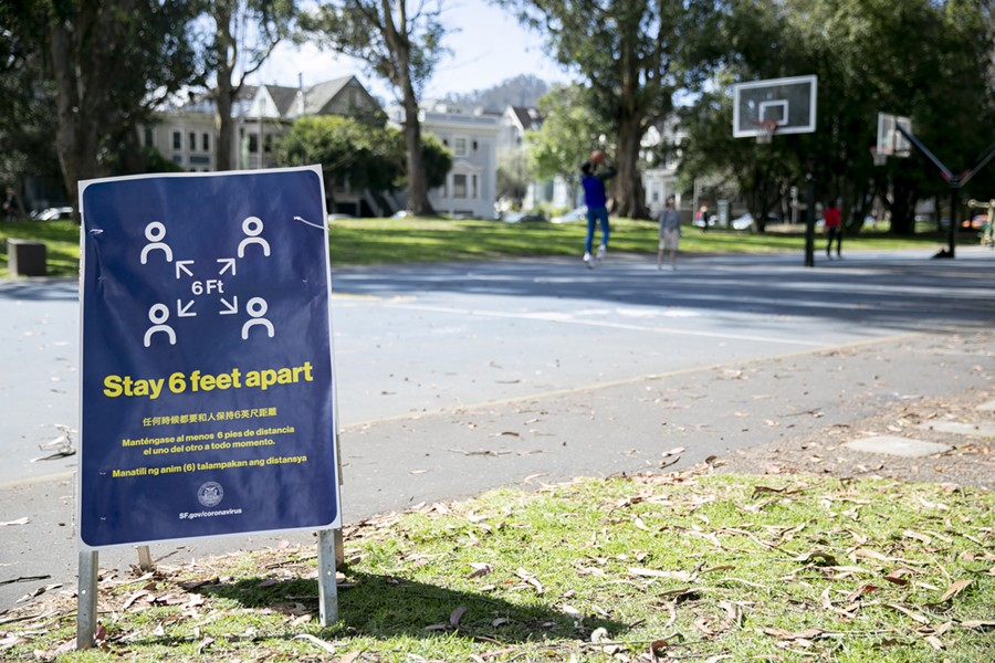 People play basketball at a San Francisco park behind a sign reminders park-goers to maintain social distancing on March 25, 2020. - ANNE WERNIKOFF FOR CALMATTERS