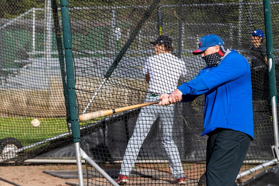 Coach Dan Joyner hits a grounder to the infield during the first day of practice. - MARK MCKENNA