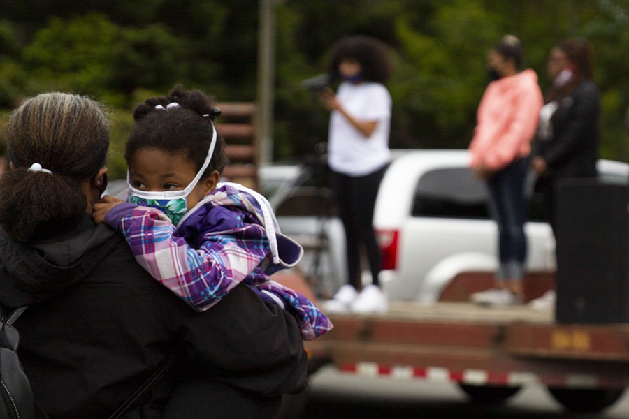 A child is held as demonstrators listen to speakers from the community at Rohner Park in Fortuna on June 5. - THOMAS LAL