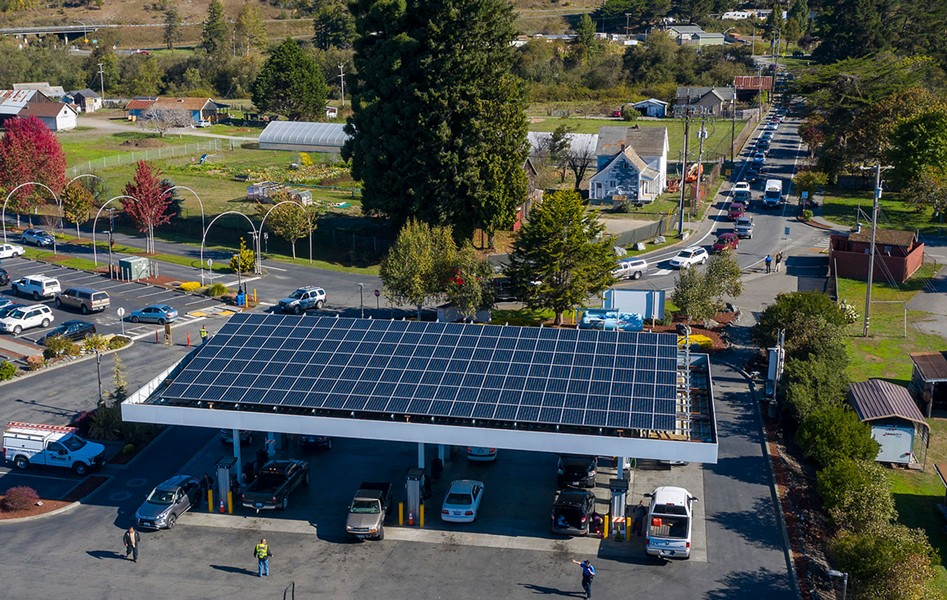 A line of cars waiting to fuel up stretches down the block at the Blue Lake Rancheria gas station, which used microgrid technology, including the solar panels above the pumps, to keep operating through the blackout. - PHOTO BY MARK MCKENNA