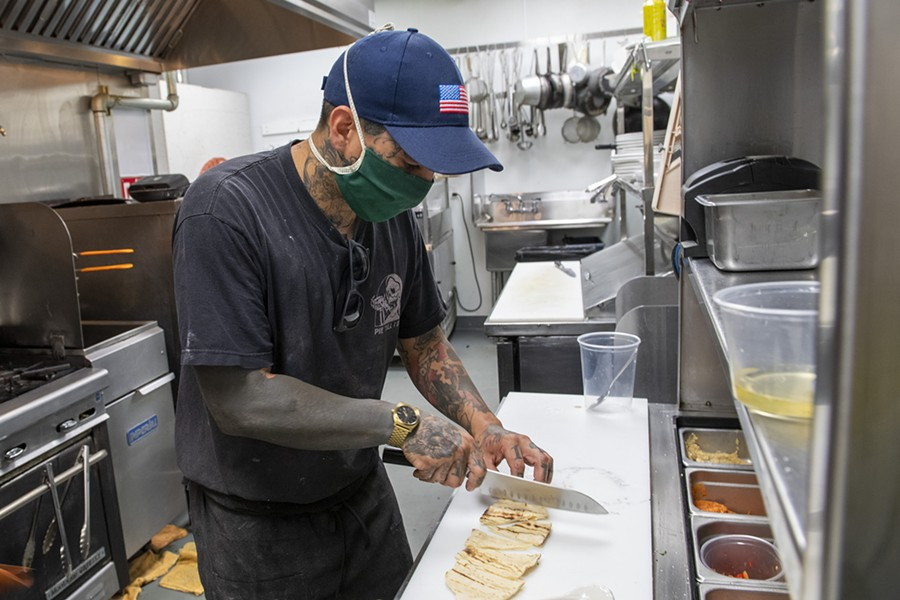 Manzanilla co-owner and sous chef Walter Rubke cuts house made pita for the mezze platter in the kitchen of the newly opened restaurant in Henderson Center. - PHOTO BY MARK MCKENNA
