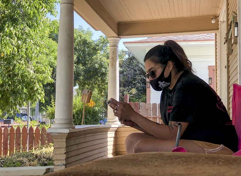 Gabriella Aldana, 24, rests on the front porch of the house she rents in Riverside on August 7, 2020. Aldana has been moving houses since she and her two children were evicted from an apartment on March 26 and expects to be evicted from her current house if the federal unemployment boost isn't approved and distributed before September 1. - NIGEL DUARA FOR CALMATTERS