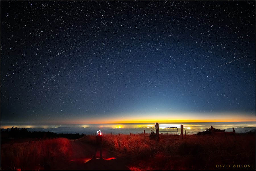 """""""Self Portrait with Perseid Meteors."""" The lights of Eureka shine on the Pacific Coast beneath a pair of Perseid meteors in this composite of two images from a timelapse sequence taken during the Perseid meteor shower of 2020 from the hills of Humboldt County on Aug. 12 - DAVID WILSON"""