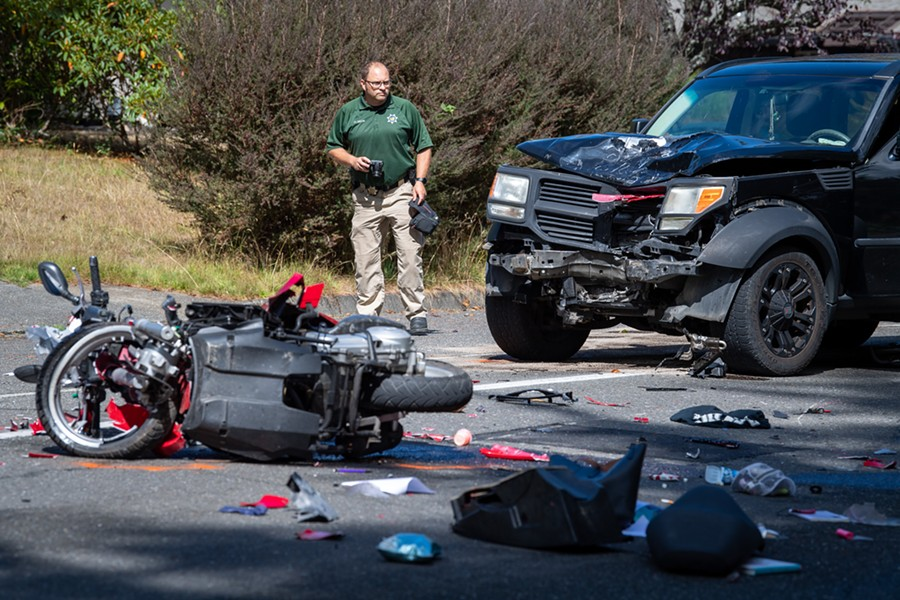Deputy Coroner Chad Zeck documents the scene of a fatal head-on collision between a scooter and an SUV on the 5300 block of Walnut Drive. - MARK MCKENNA