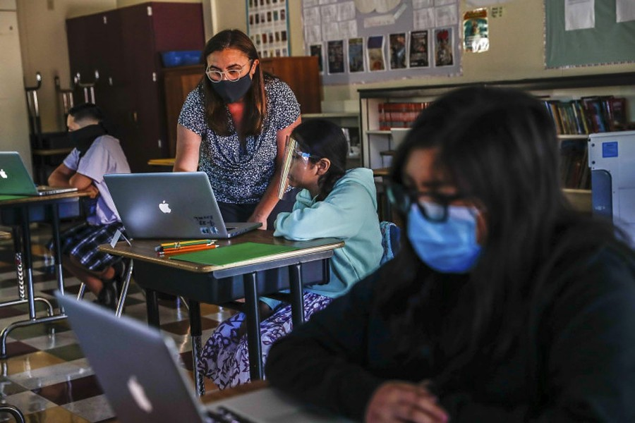 Teacher Jessica DeAnda, left, instructs Liz Valdez, 11, center, as Kayla Torres, 11, right, works on her laptop at Sunrise Middle School on June 22, 2020 in San Jose, the first Bay Area school to reopen since shelter-in-place was announced in March. - RANDY VAZQUEZ, BAY AREA NEWS GROUP