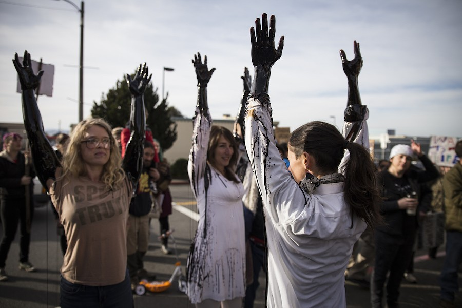 Leslie Castellano (right)  leads three other protesters letting  molasses flow down their arms in protest of Wells Fargo's investments in the DAPL. - SAM ARMANINO