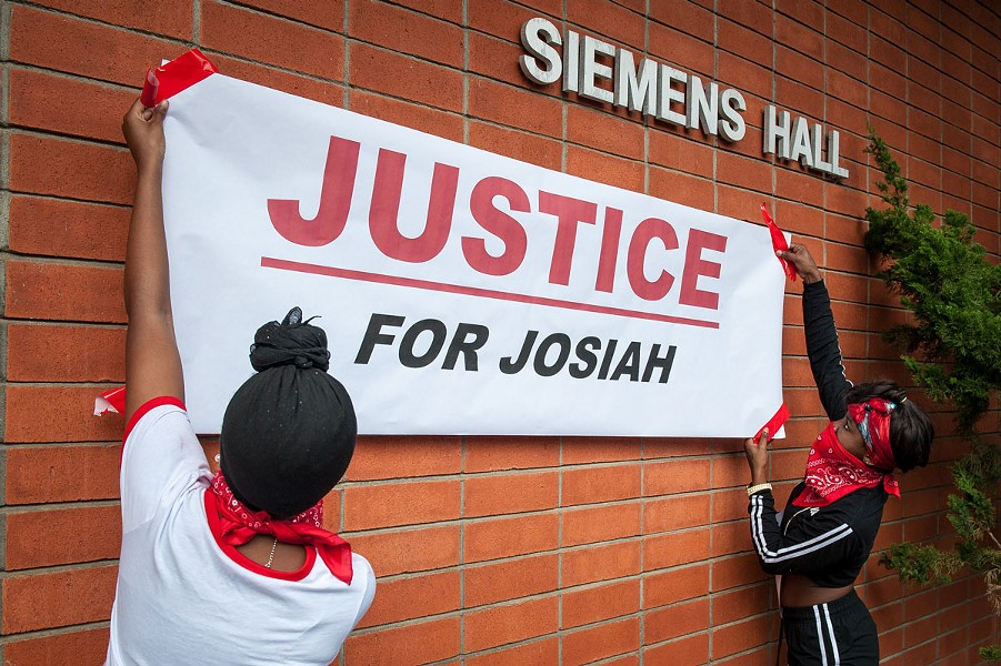 "Students hang a ""Justice for Josiah"" banner on the Humboldt State University quad. At the rally, organizers encouraged those in attendance to scrawl messages of hope, unity and protest on it. - PHOTO BY MARK MCKENNA"