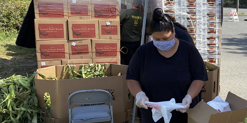 Food for People team member Veronica Brooks packing produce in preparation for a free produce distribution distribution.