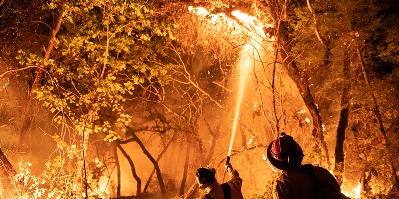 Firefighters from multiple agencies, including some that were pulled off the Monument Fire defended houses at the end of Enchanted Creek Lane on Monday.