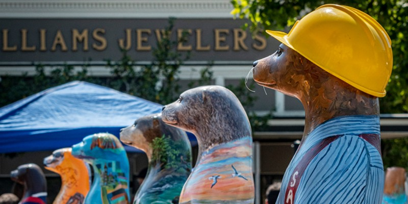 """Live In-Person Silent Auction, North Coast Otters Public Arts Initiative, Clarke Plaza, Eureka, Saturday, Sept. 11, 2021. (""""Johner the Logger Otter"""" by Claudia Lima in the foreground)."""