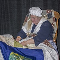 "Cannifest 2017 Betsy Ross (a.k.a. Liz DeFreanciscpo of Philadelphia) hosted the ""Weed the People"" quilting table, applying hand-made squares attendees created to her quilt. Photo by Mark Larson"