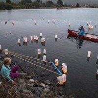 Volunteer Tony Wallin, of Arcata, helped move the lighted lanterns away from the shore into the gentle breeze blowing across Klopp Lake.