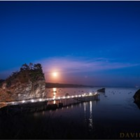 The full moon rises over Little Head, Trinidad Pier, and Trinidad Harbor. Trinidad Head is the silhouetted land mass on the right.