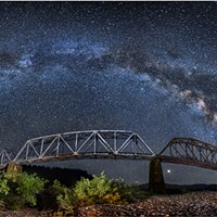 The Milky Way arcs from horizon to horizon above the South Fork Bridge in this panorama on the Main Fork Eel River, Humboldt County, California. July, 2018.